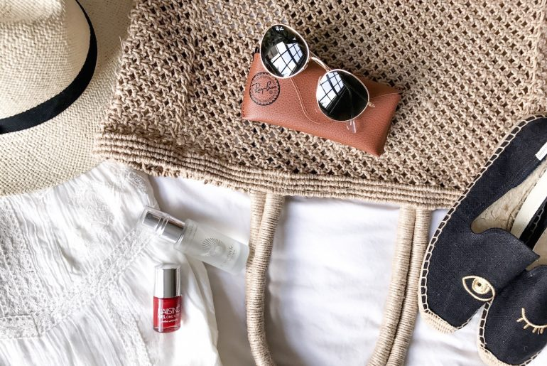 A straw hat, a beach tote, Ray Ban sunglasses, Soludos espadrilles, red nail polish and face mist are arranged in a flatlay | Wolf & Stag