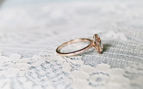 A gold and diamond engagement ring sits on a lace covered table