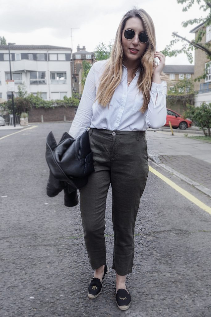 Woman walking down a London street wearing linen trousers, a white top and holding a leather jacket | Wolf & Stag