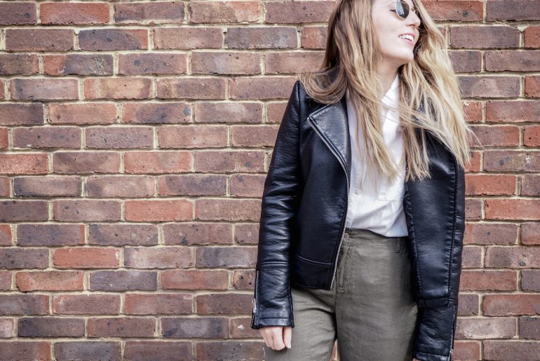 A woman standing in front of a brick wall, laughing, while wearing green linen trousers, black espadrille shoes, Ray Ban sunglasses, a white shirt and a black leather jacket | Wolf & Stag