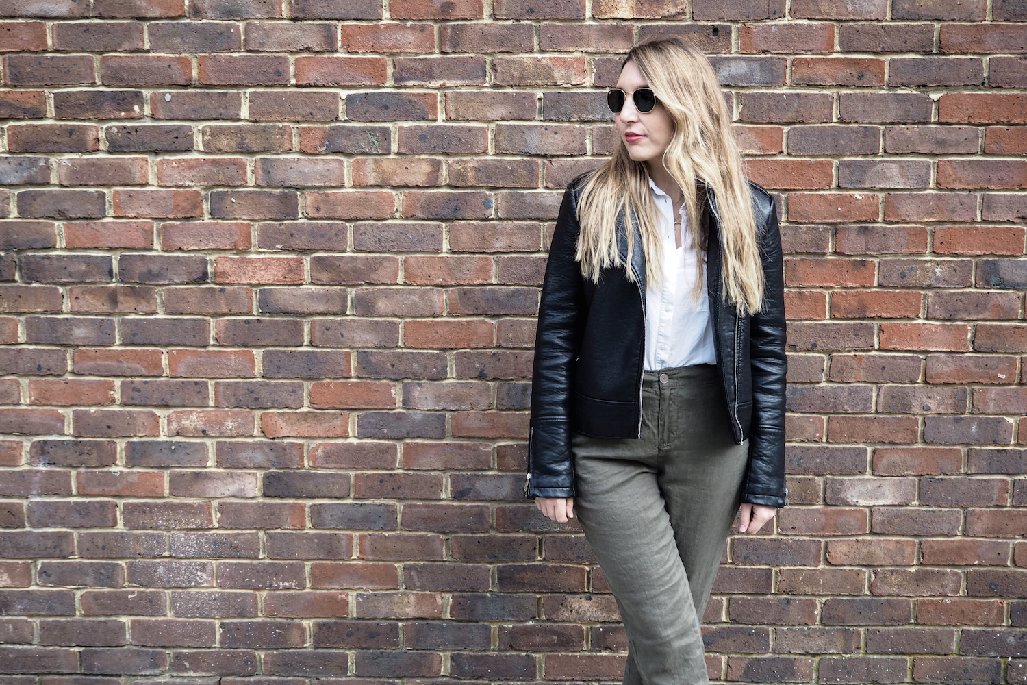 A woman standing in front of a brick wall wearing green linen trousers, black espadrille shoes, Ray Ban sunglasses, a white shirt and a black leather jacket | Wolf & Stag
