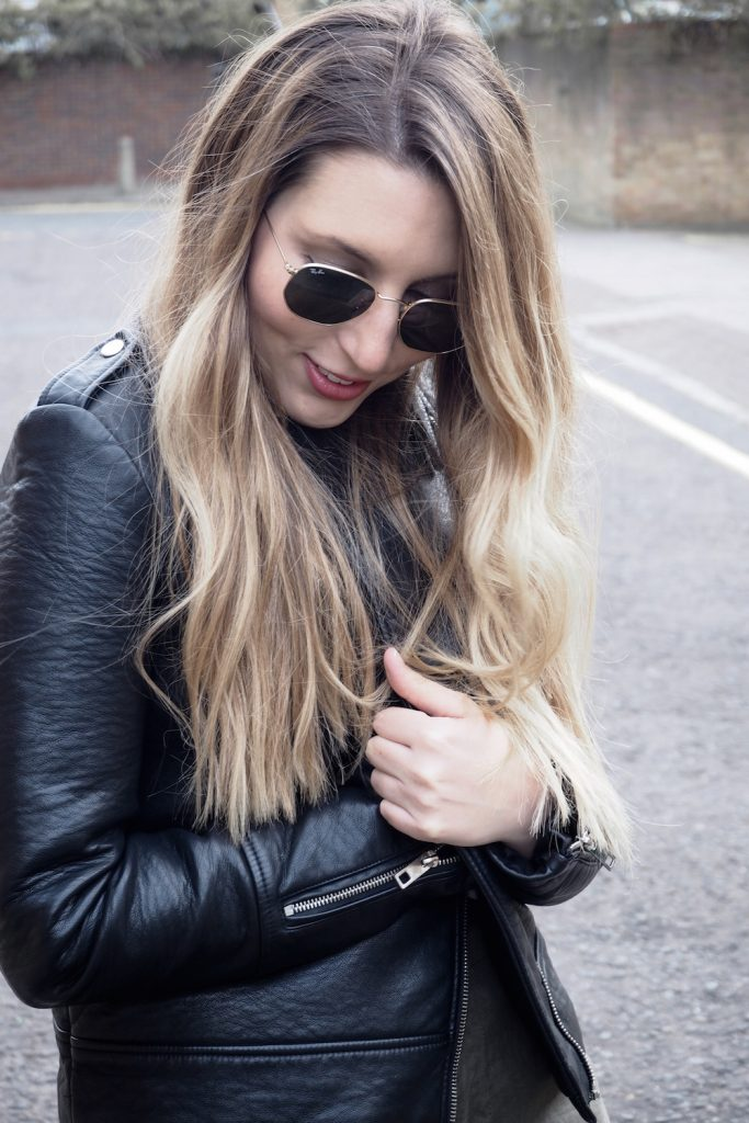 A woman wearing a black leather jacket and Ray Ban sunglasses tilts her head down to look at her linen trousers