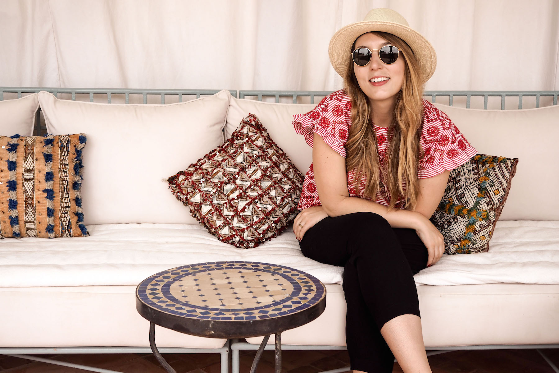 Eire Pollard in a Zara red top, Hush black cottons trousers, Ray Ban sunglasses and a hat on top of the Riad Kniza, Marrakech